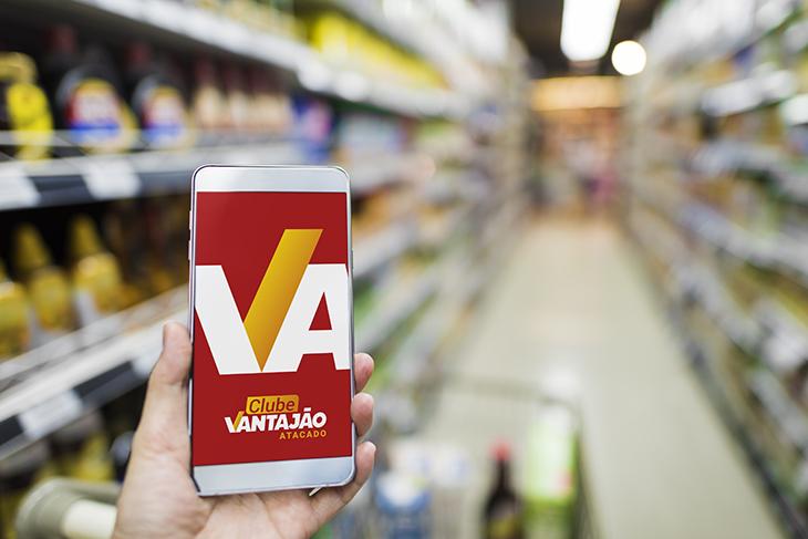Foto focada em um celular, que está quase ao centro da imagem. Ele é branco, e a sua tela também está branca. Ao fundo, em desfoque, podemos ver as prateleiras e um carrinho de supermercado.