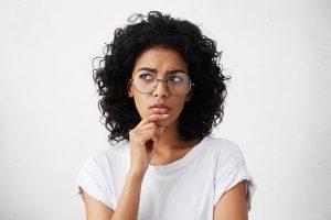 Foto de mulher negra, com cabelos cacheados, que usa óculos e camiseta branca. Ela está com a mão no queixo, transmitindo uma sensação de dúvida.