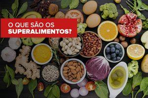 Na imagem sobre uma superfície preta estão dispostos diversos alimentos saudáveis. Abacate, laranja, alho, gengibre, cebola, tomate, brócolis, ovos, dentre outros.