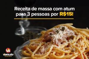 Na imagem, um prato com massa e atum está posicionado sobre uma superfície preta. A massa, espaguete, está por baixo e, no topo, pode-se ver um pedaço de atum e uma porção de queijo ralado.