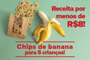 Na imagem há uma banana metade descascada ao lado de um saco de papel pardo, com diversos chips de banana dentro. Algumas rodelas do lanche estão espalhadas para fora da embalagem.