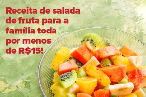 Na imagem é possível ver uma salada de frutas com manga, banana, mamão, abacaxi e kiwi dentro de uma tigela de vidro transparente.