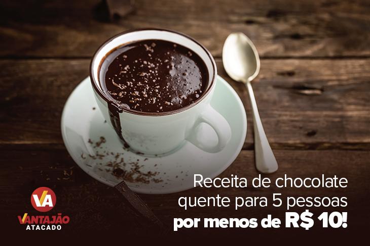 Na imagem é possível ver uma xícara branca cheia de chocolate quente. A bebida tem raspas de chocolate em cima e escorre pela borda da xícara. No pires está um pedaço de chocolate.