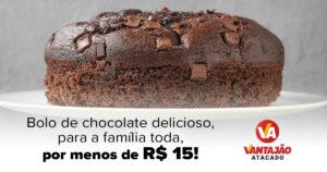 No centro da imagem, sobre uma forma branca elevada, está um bolo de chocolate redondo, com pedaços de chocolate no topo. O fundo da imagem é cinza.