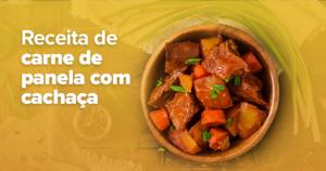 Dentro de uma tigela marrom arredondada, sobre uma mesa de madeira, estão pedaços de carne cozida com cenoura, cebola e salsinha. Sobre a mesa, ao redor da tigela, estão temperos como pimenta, cebolinha e alho.